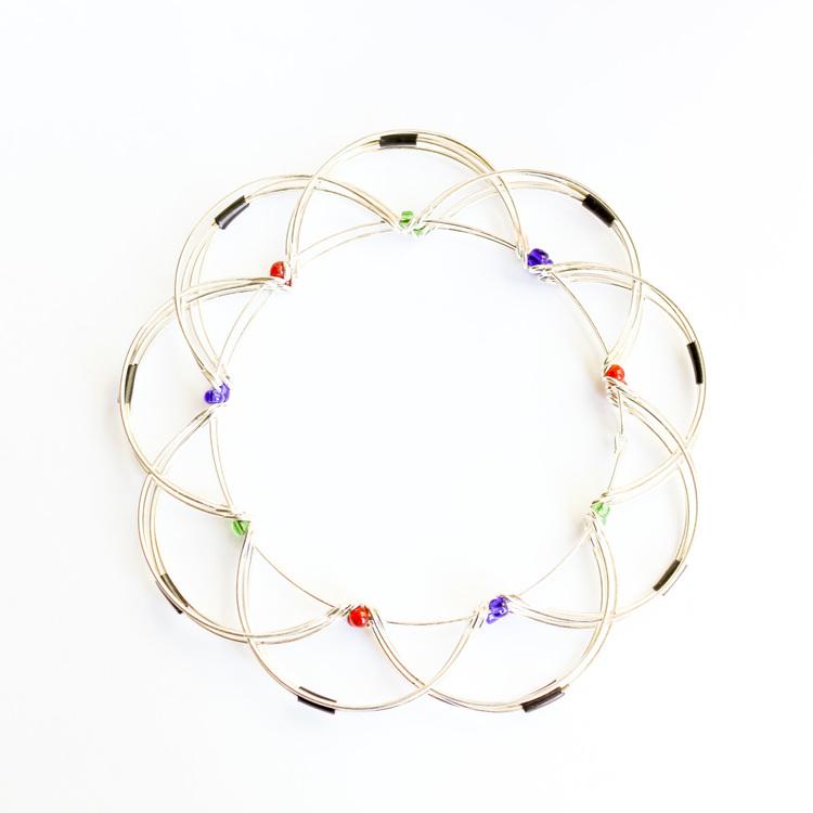 Mandala i form av lotusblomma av metalltråd med glaspärlor. Hopfälld.
