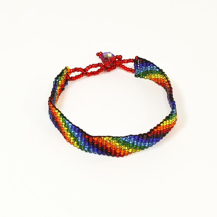 Armband i regnbågsfärger, sammansatt av mycket små glaspärlor, knäppt.