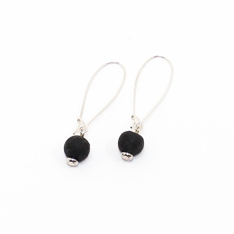 Ett par örhängen med var sin svart pärla av återvunnet glas.