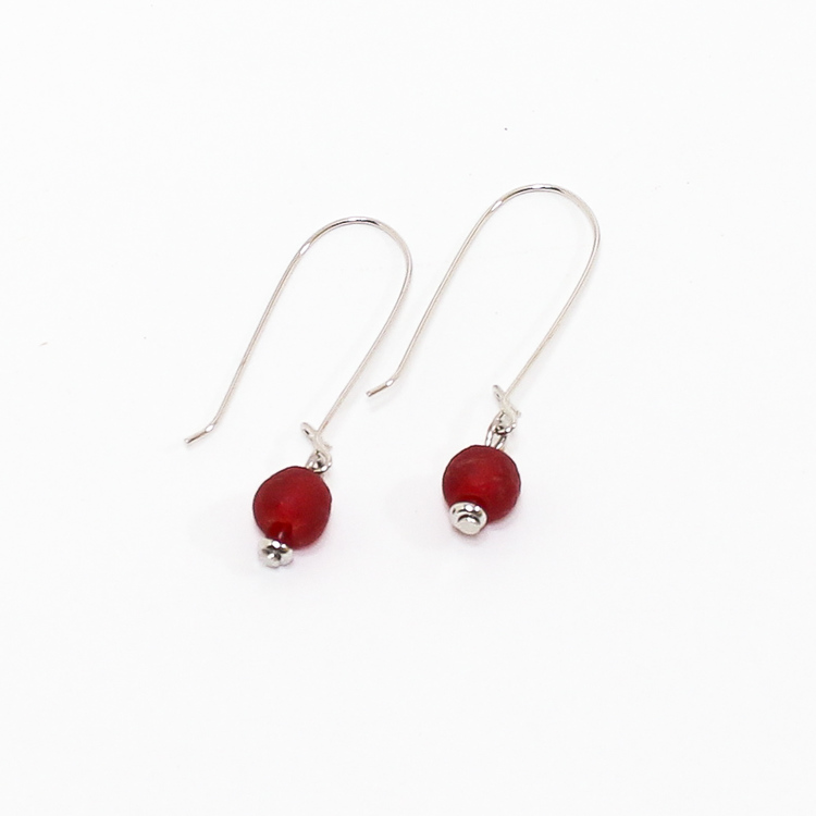 Ett par örhängen med var sin röd pärla av återvunnet glas och försilvrad metall.