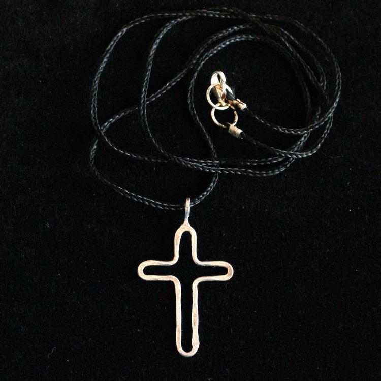 Vackert silverfärgat kors i svart flätat tunt band, kan förkortas. Mässing. Nickelfritt smycke. Hängsmycke. Svart backgrund.