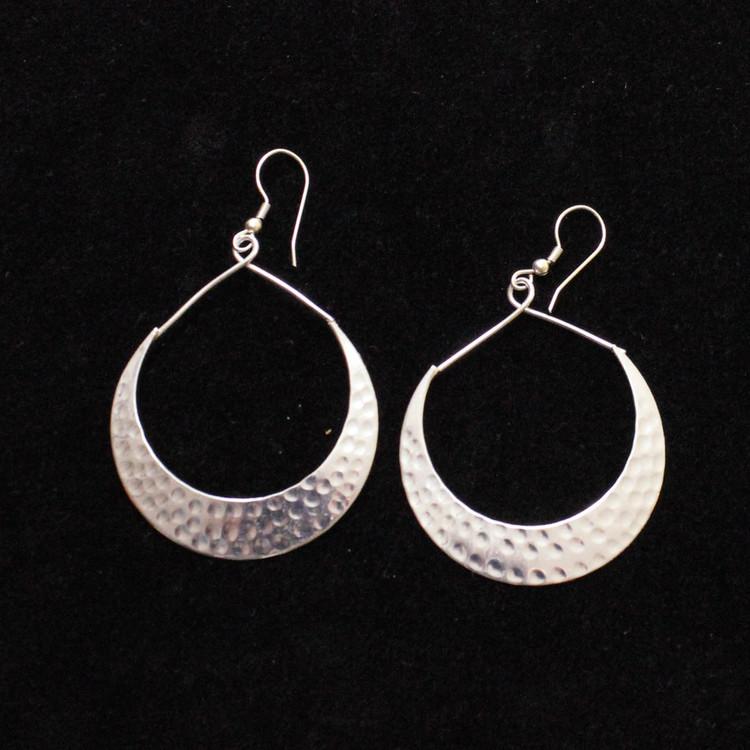 Stora vackra örhängen med hamrat mönster, silver, vitmässing, ett indiskt smycke, etisk handel. Svart bakgrund.