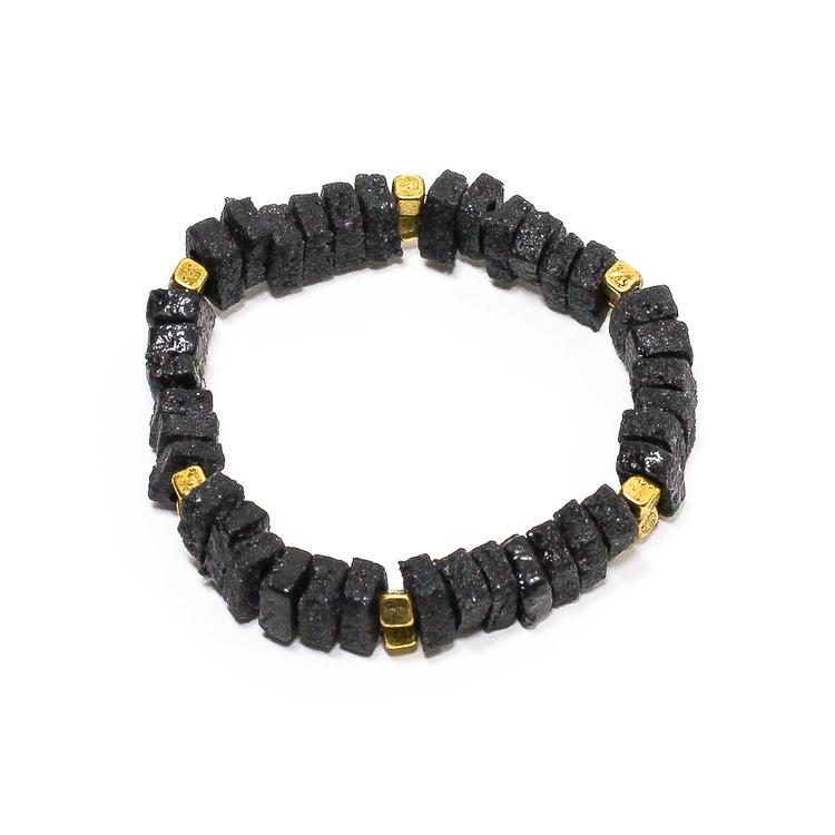 Armband med fyrkantiga svarta glaspärlor och guldfärgade metallpärlor. elastiskt band.