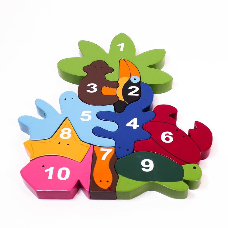 Pussel med siffror 1 - 10. Motiv är olika djur och en palm i fantasifulla former. Förvaras i en påse med plast på ovansidan så man kan se innehållet.