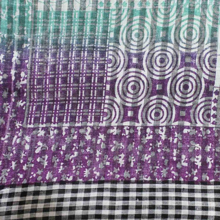 Sjal, scarf, halsduk i handvävd bomull med tryckt mönster i gröna, lila & svarta toner på vit botten. Detaljbild.