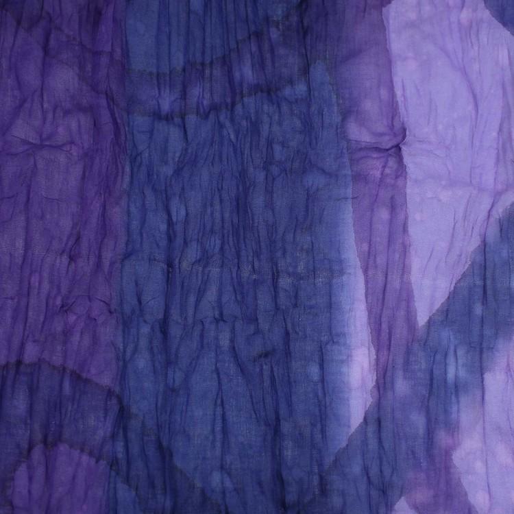 Stor färgstark sjal i krinklad bomull, lila och blå nyanser, med små vita stäng. Detaljbild.