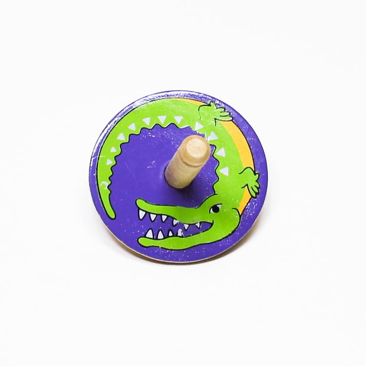 Klassisk, enkel snurra i trä med en krokodil målad på ovansidan. Känd även som spinner eller spinning top. Leksak för barn.