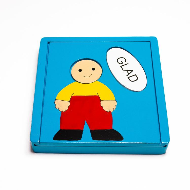 Träpussel i låda, motiv olika känslor. Ansiktsuttryck/emojis paras ihop med rätt ord: glad, ledsen, arg, sur, rädd. Lådans framsida.