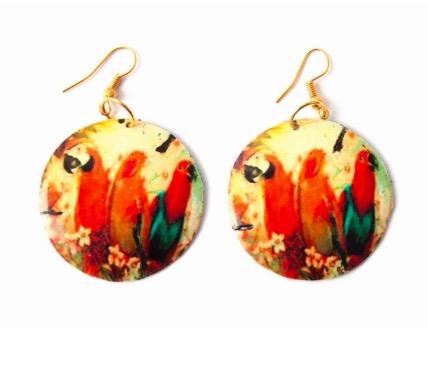Örhänge i mässing, klara varma färger. Motiv tre ara-papegojor, kloka fåglar med ett milt temperament.  Fair Trade.