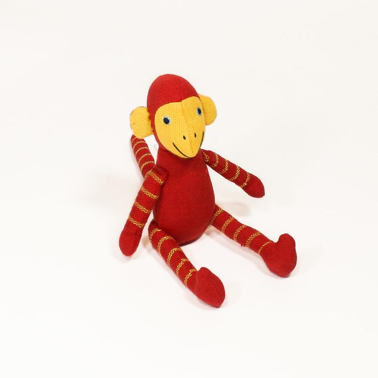 Sittande apa i tyg, klarröd. Kroppen, huvud, armar & ben med gula ränder, även på svansen. Ljusa öron & händer, sött & vänligt ansikte. Charmig som maskot!