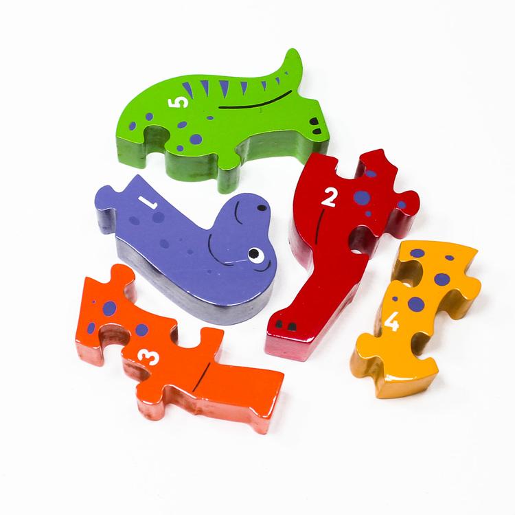 Snäll , färgglad dinosaure som träpussel, med siffrorna 1 -5 på ena sidan. Här är pusslets delar inte sammansatta. Rekommenderas till barn äldre än 1 år. giftfria färger. Fair Trade.