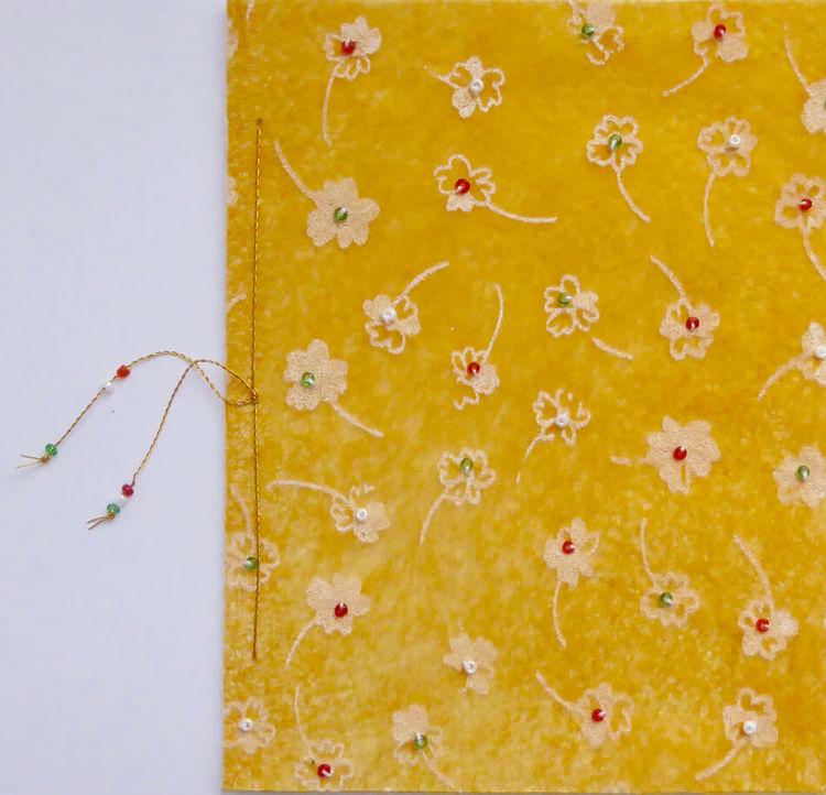 Vikt hälsningskort, på framsidan gult färgat och med målade små vita blommor som har små pärlor påsydda i mitten. Fastsydd pappersark att skriva på. Handgjort.
