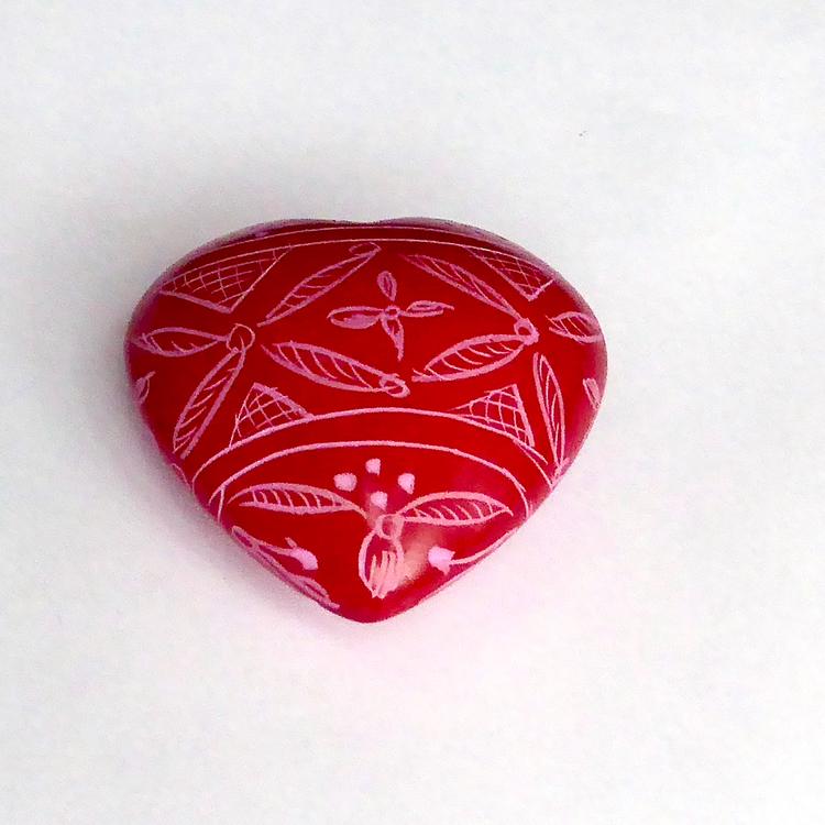 Dekorativt litet rött hjärta med vackert mönster. Ett en hjärtevän. Handgjort av täljsten i Kenya för Fair Trade.