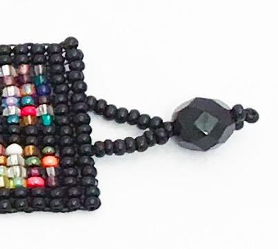 Armband av små glaspärlor, grafiskt mönster. Detalj på slutstycket, hank. Fair Trade.