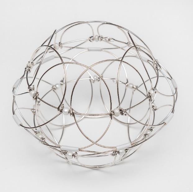 Mandala i form av lotusblomma av metalltråd med glaspärlor. Här är pusslet format som klot.
