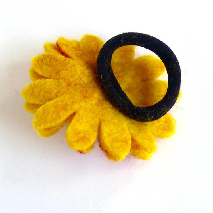 Hårsnodd med lagom stor tovad solros i gul och röda nyanser. Blomkorgen med dekorerad med små glaspärlor. Baksidan med elastisk hårband.