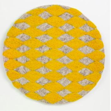 Handtovad sittdyna Felt Harlequin från Afroart. Varmgul och grå färg. Diameter 38 cm.