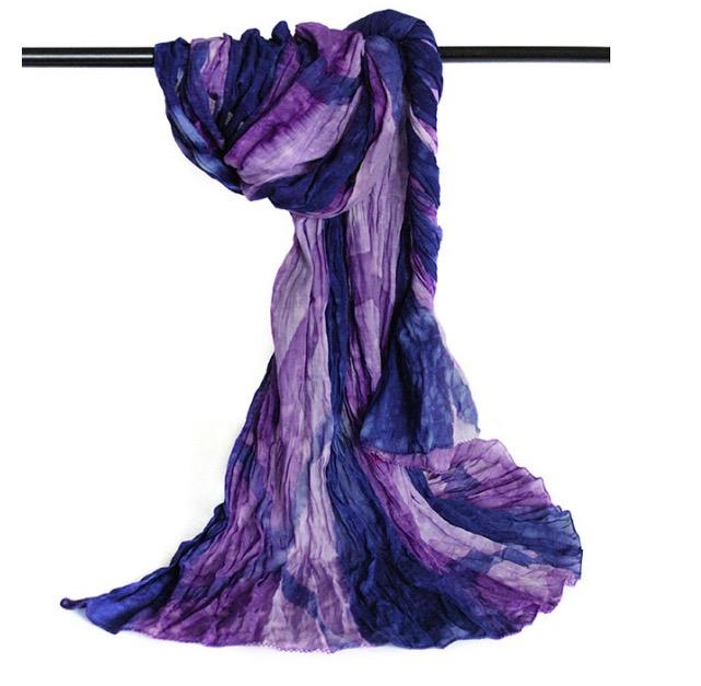 Stor färgstark sjal i krinklad bomull, lila och blå nyanser, med små vita stäng. Fair Trade.