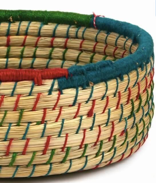 Rund, öppen korg i naturfärgad jute, dekorerad med färgat gräs. Detaljbild. Handflätad i Bangladesh.