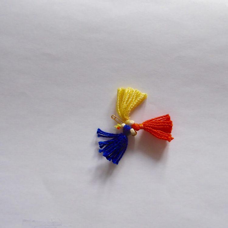 Liten ulltofs i blå, röd, gul. Mot den grå bakgrund är tofsen en fin accent på scarfen.