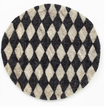 Handtovad sittdyna Felt Harlequin från Afroart. Svart och grå mönster. Diameter 38 cm.