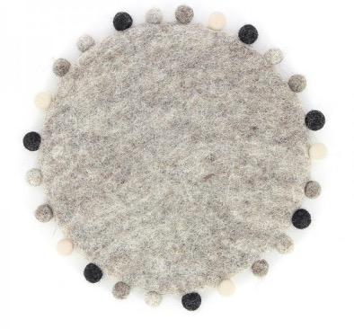 Runt underlägg till gryta, ljusgrå med små bollfransar i omväxlande svart och grå. Handtovat i Nepal, för Fair Trade.