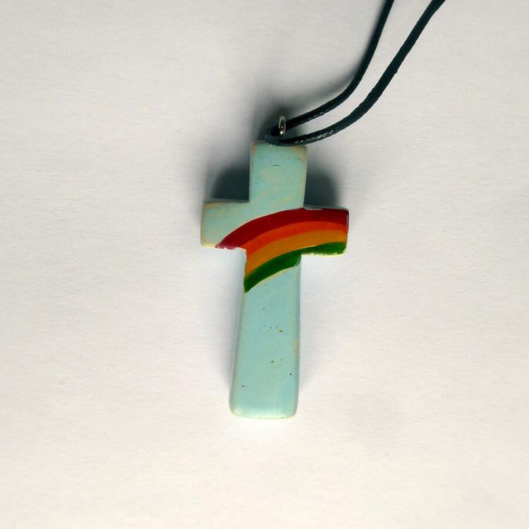 Halssmycke Kors i täljsten med påmålad regnbåge som hängsmycke. Med kraftigt bemullssmöre, längden kan varieras.Fair Trade från Kenya.