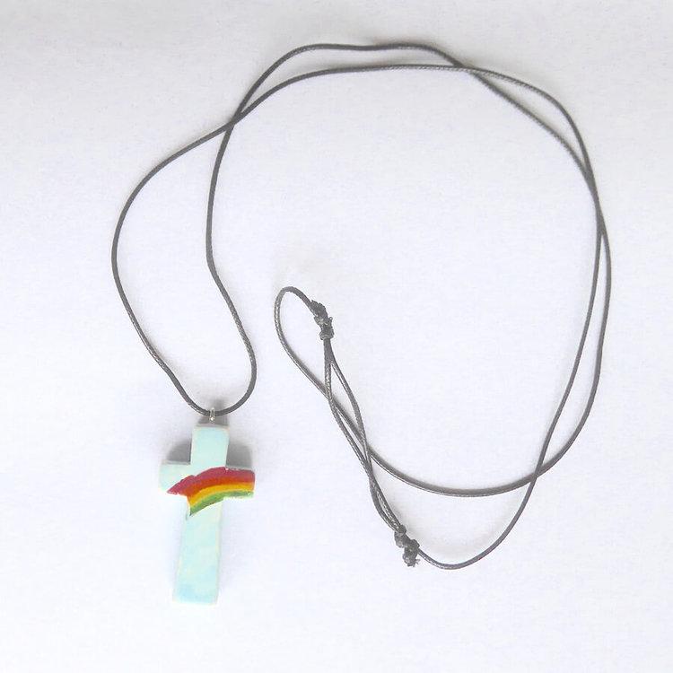Halssmycke Kors i täljsten med påmålad regnbåge som hängsmycke. Med kraftigt bemullssmöre, längden kan varieras. Fair Trade från Kenya.