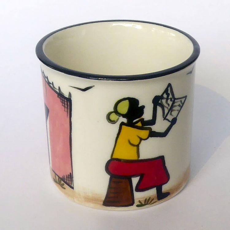 Mugg i keramik, på utsidan glad vardagsscen från Sydafrikas townships. Läsende kvinna på pall. Kapula keramik för Fair Trade.
