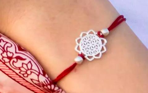 Armband med livets blomma-motiv i mässing. Justerbart band av mörkröd bomull. Fair Trade från Indien. Dekorationsbild.