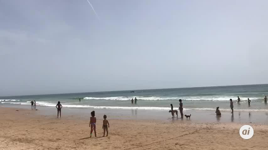 Una patera con inmigrantes llega a una playa repleta de Barbate