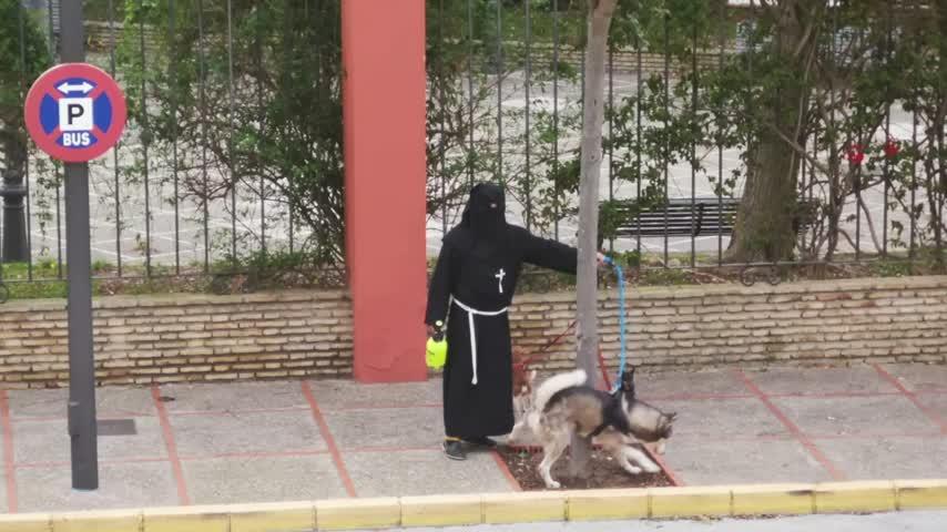 Vestido de penitente y con sus perros en el Parque de las Huertas
