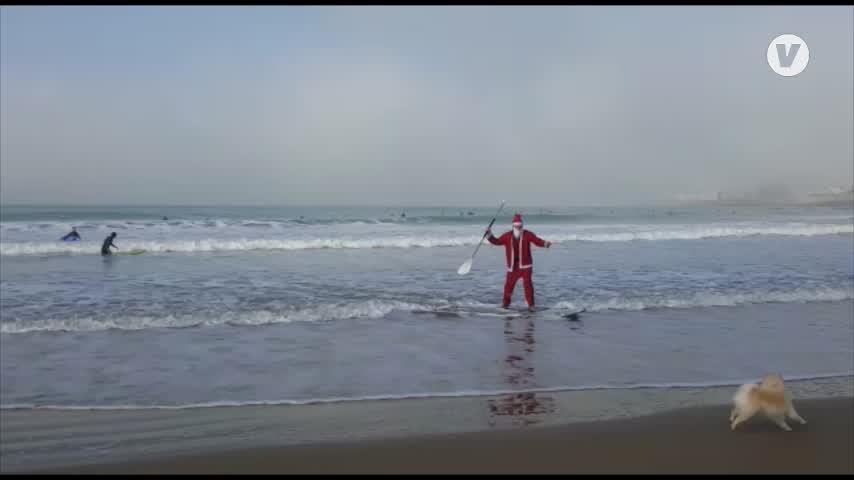 Papá Noel llega surfeando a una playa de Cádiz capital