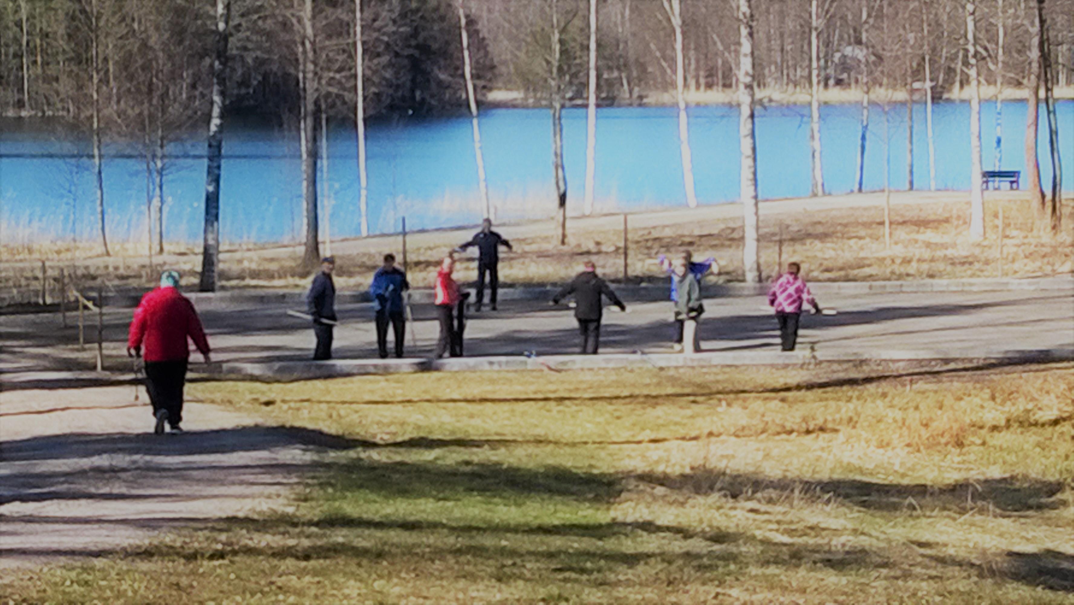 Ihmisiä järven rannassa keppijumpassa