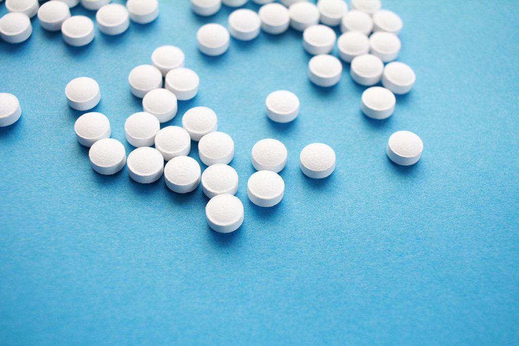 Valkoisia pillereitä sinisellä taustalla