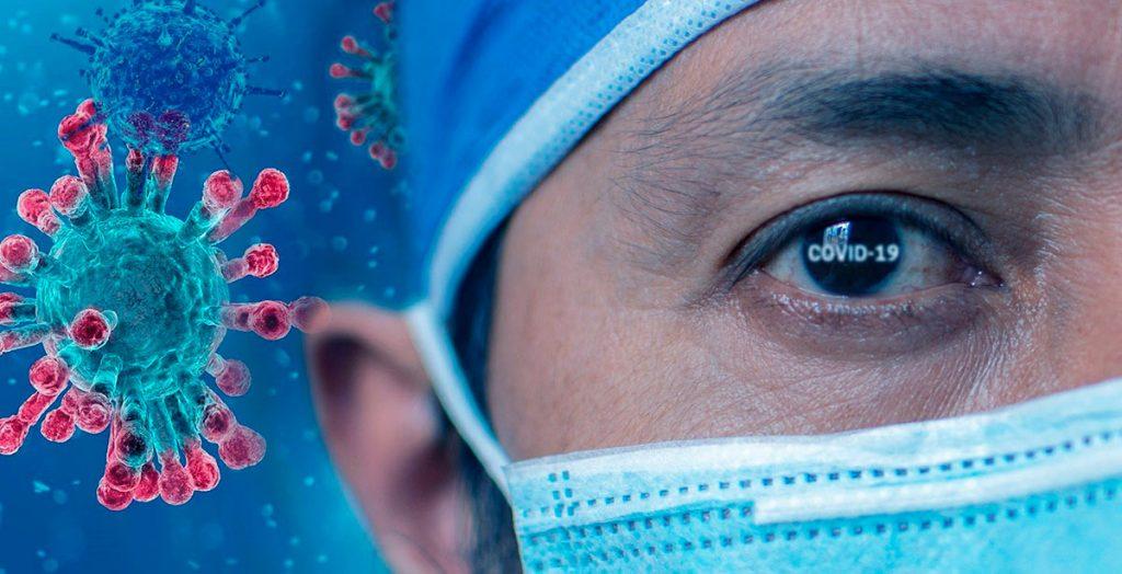 Koronavirus ja lähikuvaa mieslääkärin kasvosuojaimella peitetyistä kasvoista