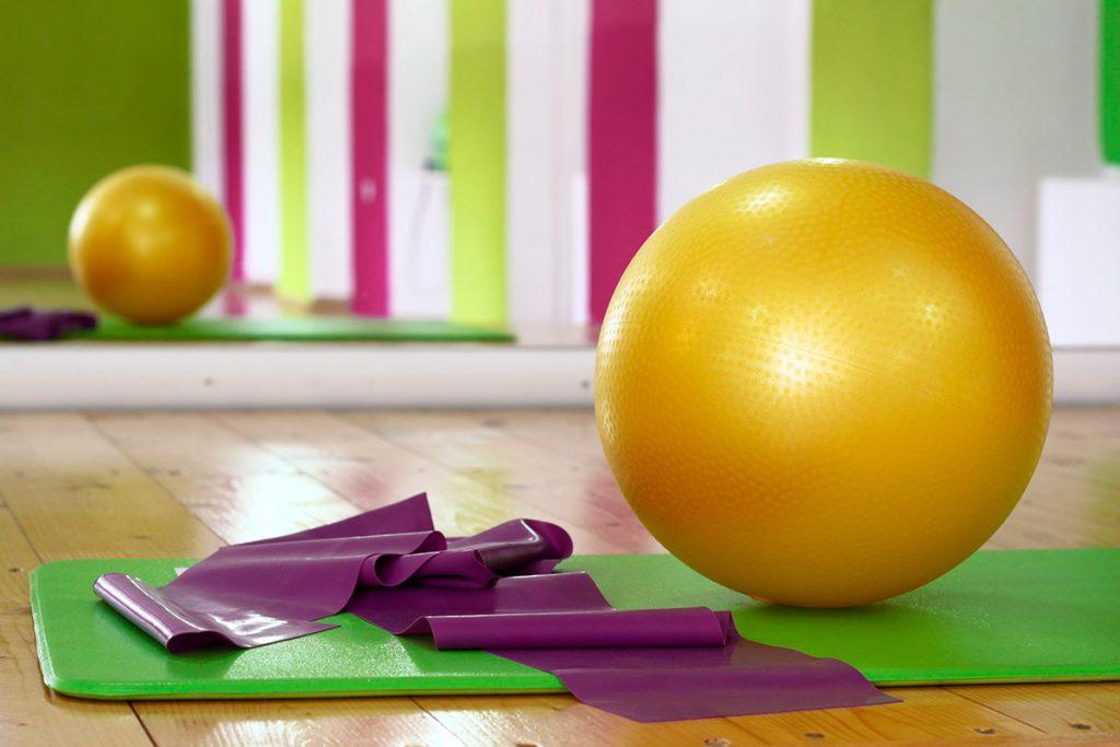 Jumppapallo, kuminauha ja jumppamatto pilatesstudion lattialla