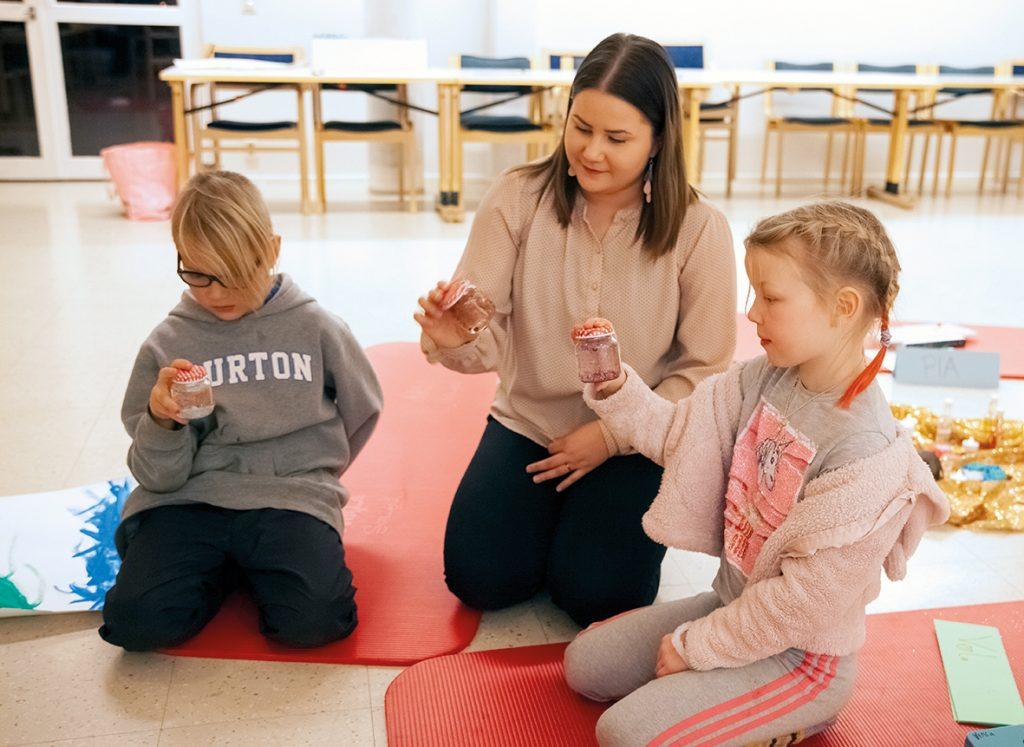 Kuvassa keskellä lastentunnetaito-ohjaaja Pia Ilves sekä hänen vierellään ryhmään osallistuneet Toivo ja Venla. Kolmikko tutkailee tekemiään huminapurkkeja.