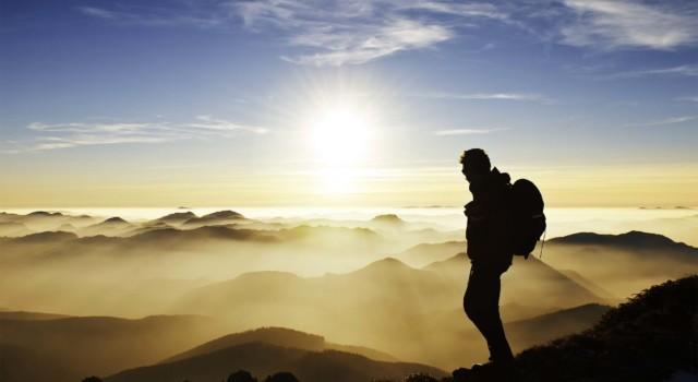 Hiker on mountain at sunset