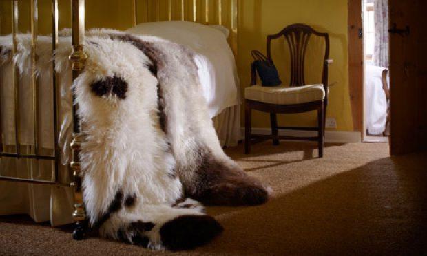 Bespoke sheepskin rug draped over bed