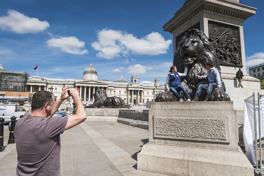 London tourists in Trafalgar Square UK