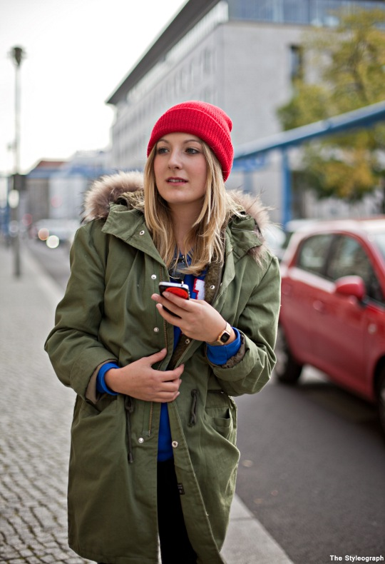 Street fashion shot of a woman in green parka and red cousteau cap clutching smart phone