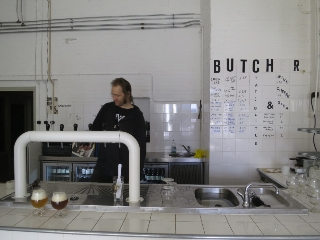 Man pouring beer behind a bar in a former abattoir