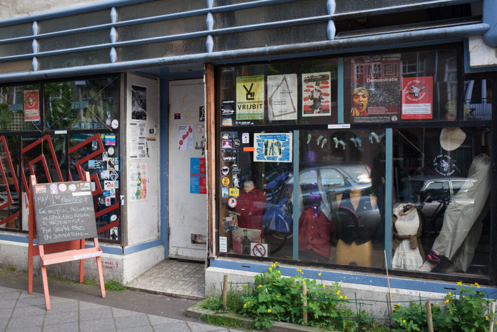 The outside of a venue with big windows and lots of posters in it.