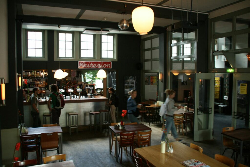 The interior of a bar with some people in it during the day