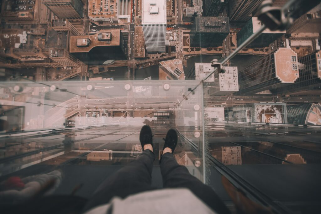 First person perspective of a man looking down through a glass floor from Skydeck Chicago