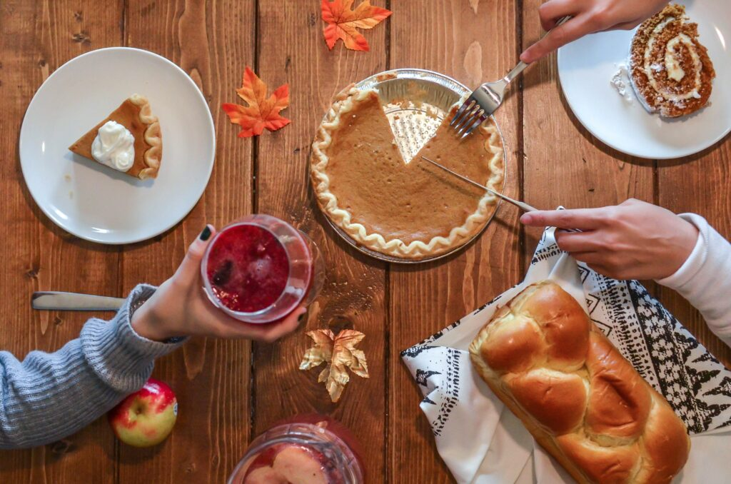 A bird's eye view of  pumpkin pie being served on a table decorated with crisp, autumn leaves