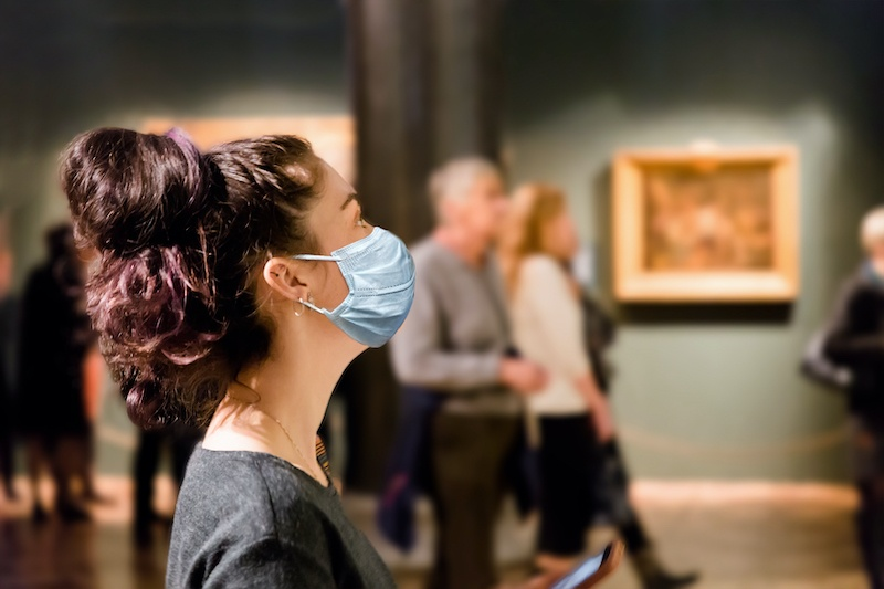 A woman wearing a mask looking at a painting