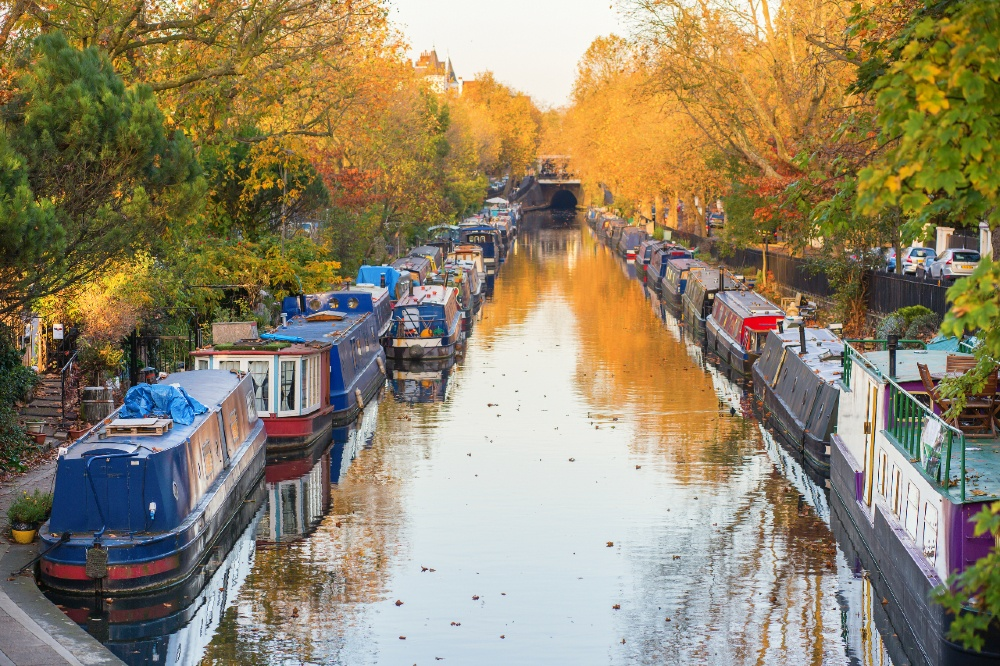 Narrow canal lined with barges. Yellow and green trees frame the canal.