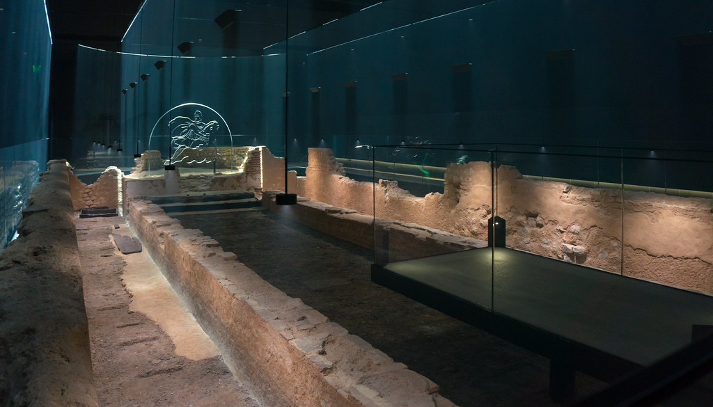 Remains of the Mithraeum in a dark underground space. Glass sculpture of man of horse is seen in background.